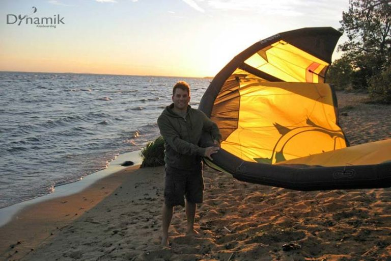 Chad the owner of Dynamik Kiteboarding holding a kiteboarding kite on a beach