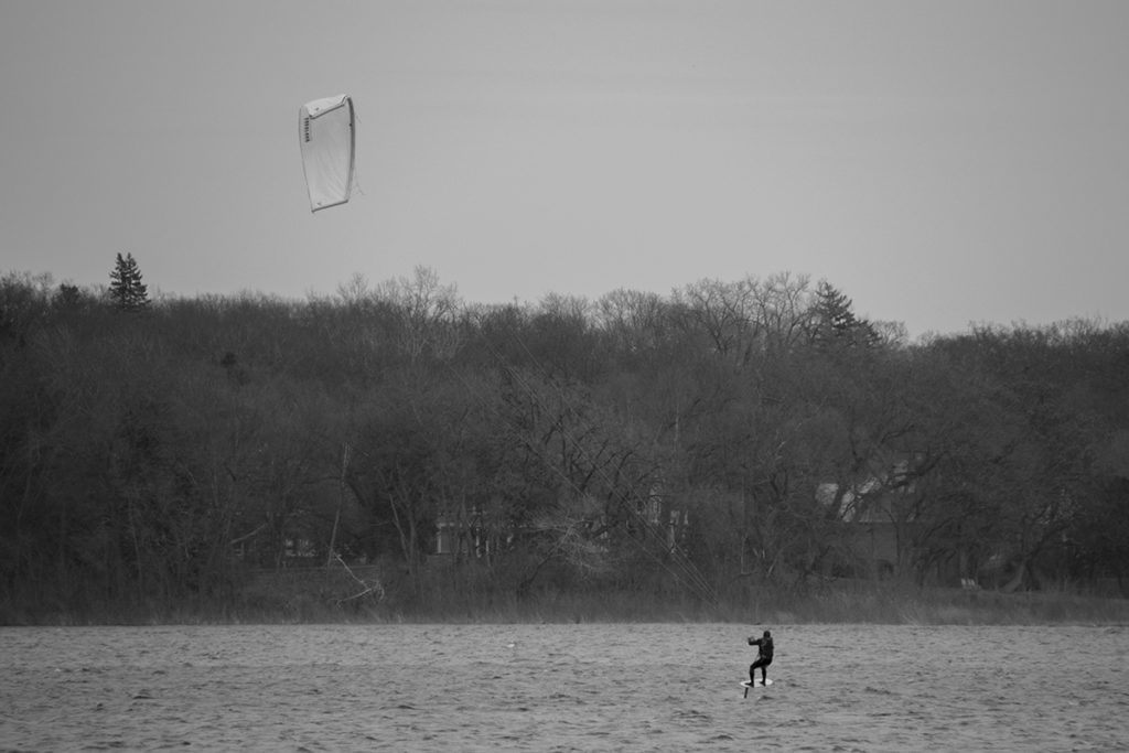 A kiteboarder on a foil board lifts off the water.
