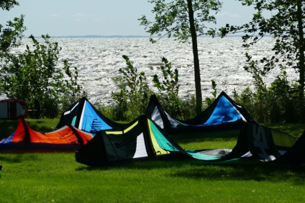 Kiteboarding kites sitting on green grass overlooking Lake Mille Lacs