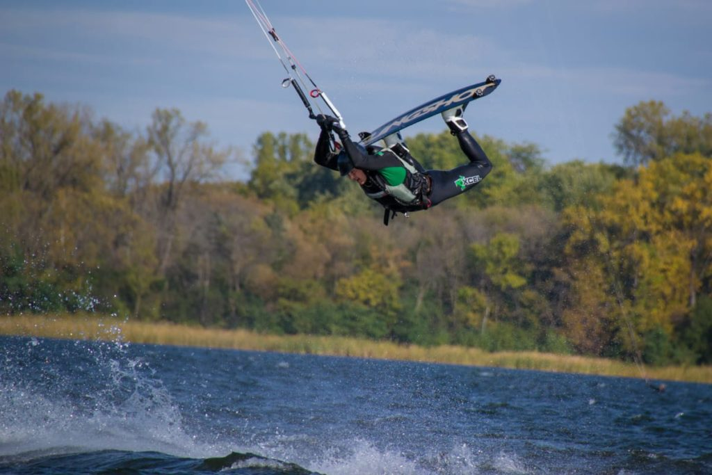Kiteboarder performing a trick with fall colors in the background and water splashing