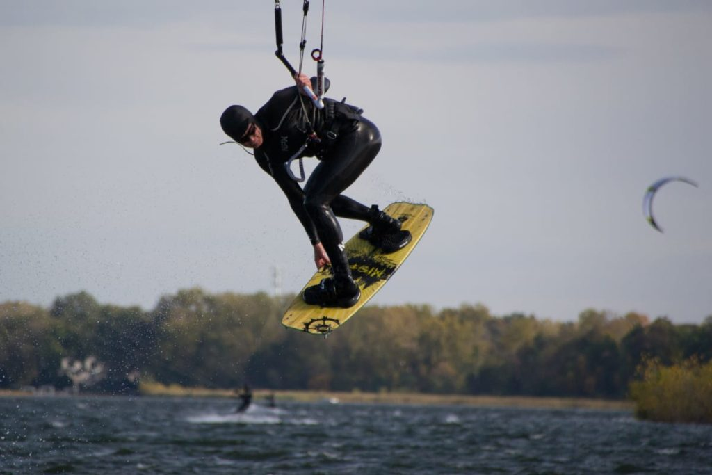 Kiteboarder grabbing his board while wearing a wetsuit