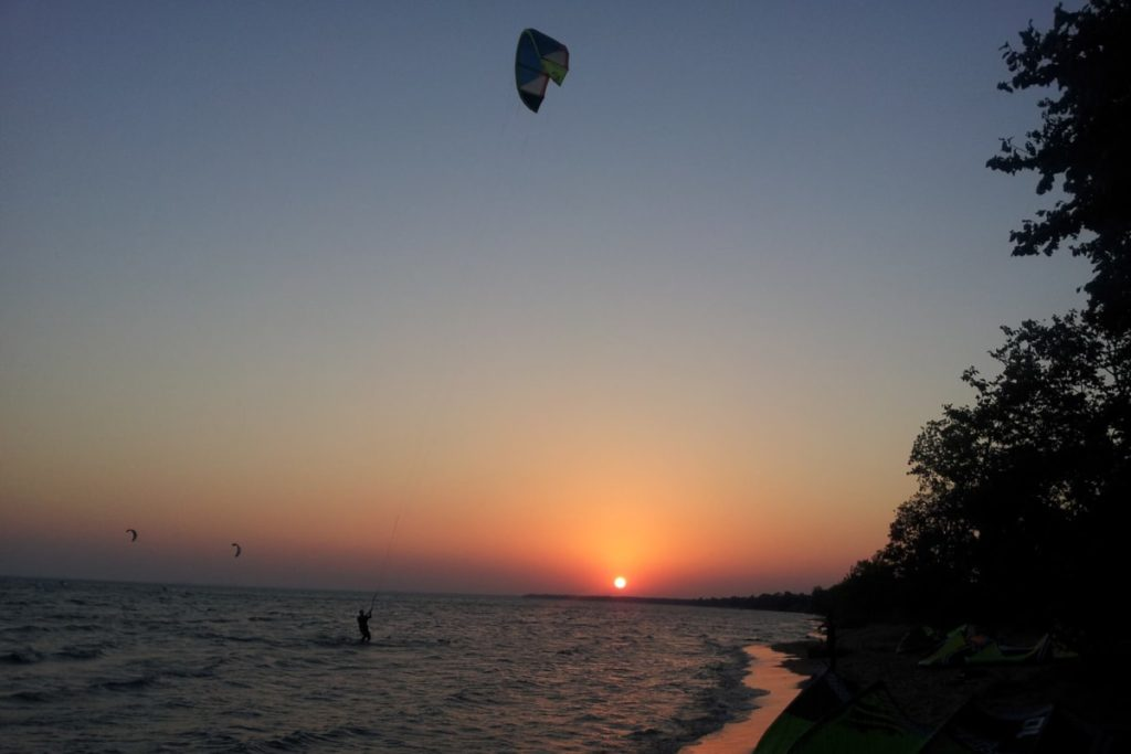 Kiteboarder in the water with the sunset in the background