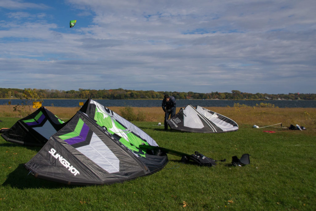 A kiteboarder is rigging a kite up on the shore of White Bear Lake