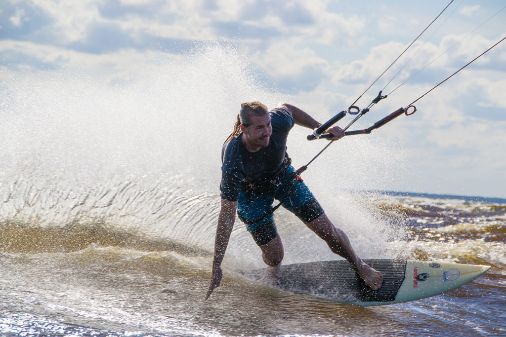 A kitesurfer slashes a wave with a large smile on his face.