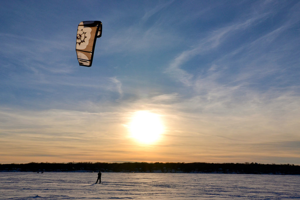 A kiteboarder rides across a frozen lake on his snowboard with the sunset in the background.