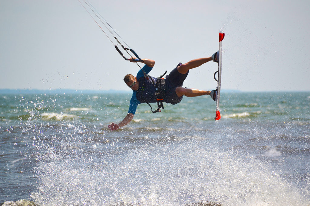 A kiteboarder jumps above the water on a sunny day.