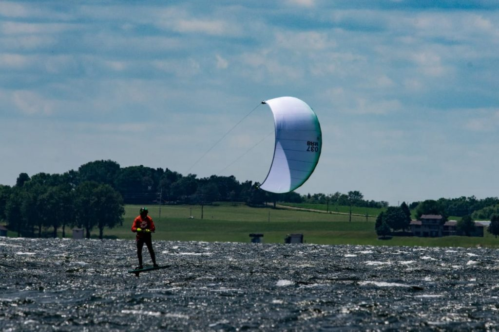A kiteboarder glides across a windy lake