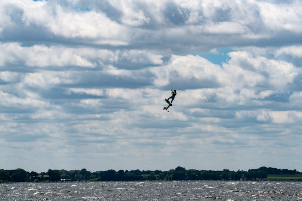 A kiteboarder jumping really high off the water