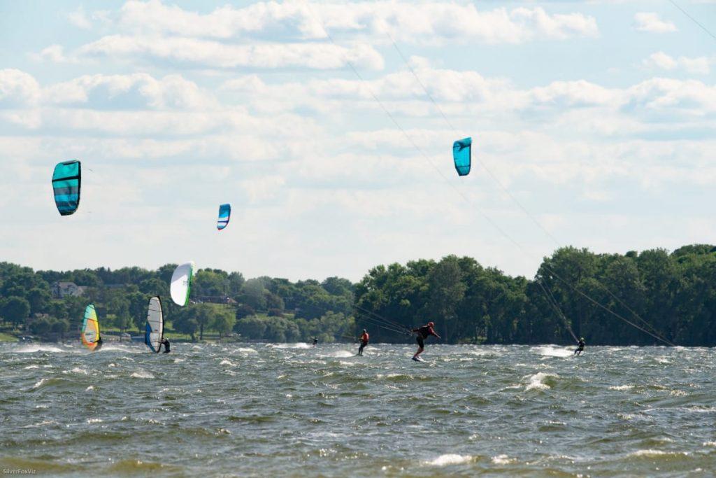 Kiteboarders and windsurfers on a windy lake