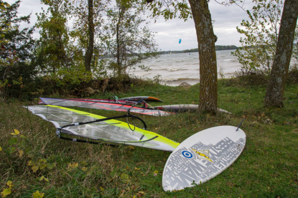 Windsurfing boards sit on the grass at Lake Waconia