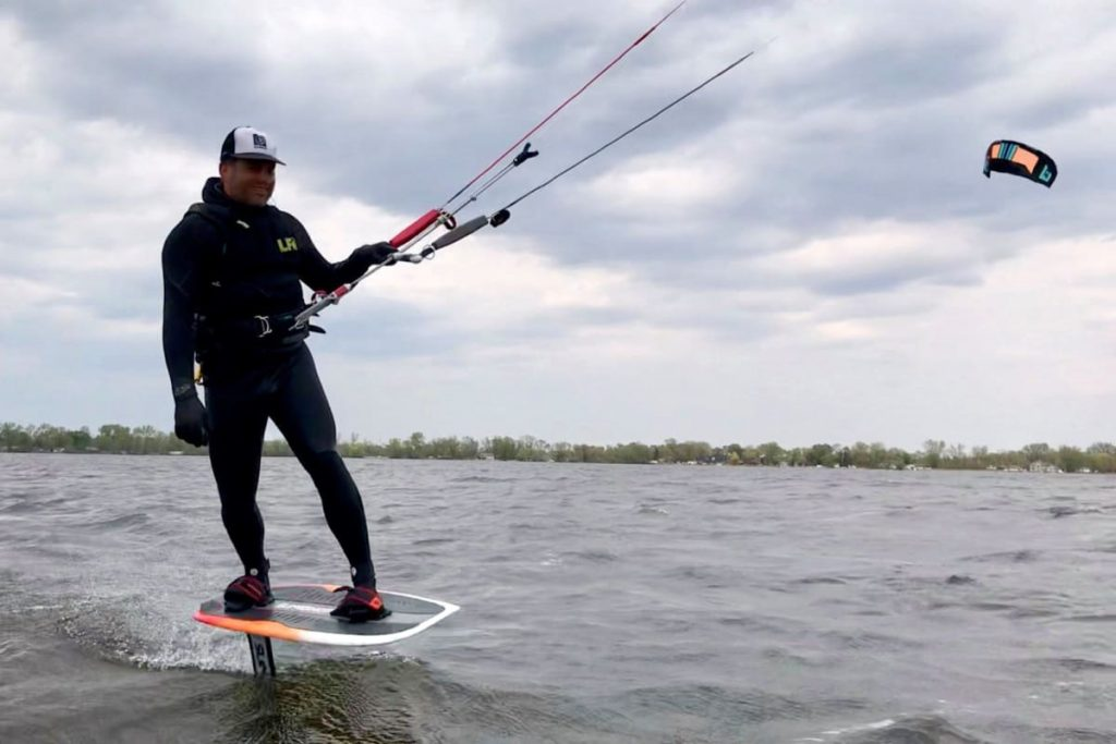 A foilboarder gets close to the camera on a windy lake